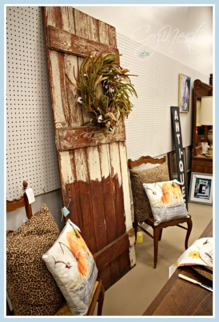 Barn door flanked by vintage chairs